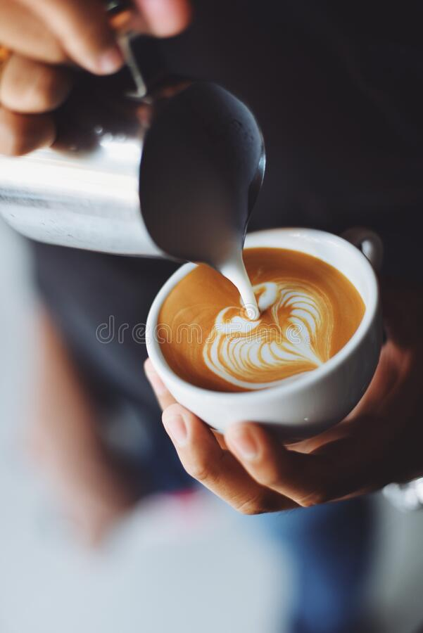 Adding milk to cappuccino royalty free stock images
