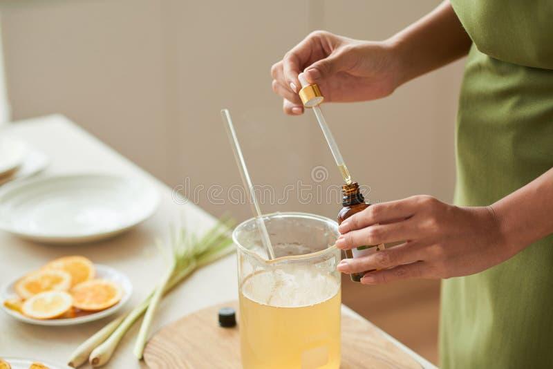Adding oils into soap mixture stock photos