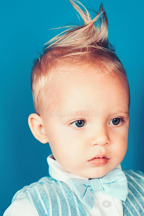 Adding some care to my hair. Small child with messy top haircut. Hair styling products. Small boy with stylish haircut stock image
