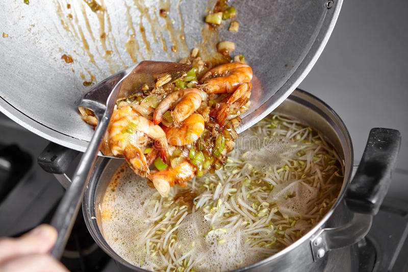 Adding the stir fried to the soup. Adding the stir fried shrimp with leek and garlic to the soup royalty free stock photos