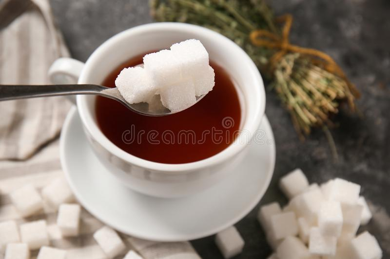 Adding of sugar to cup with aromatic tea on grey table royalty free stock photo