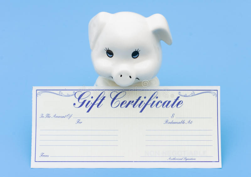Adding to your Savings. A piggy bank sitting with a gift certificate on a blue background, Adding to your Savings stock image