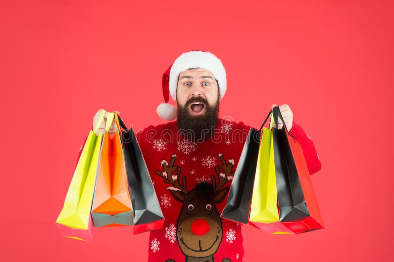 Additional services. Save on purchases. Shopping with joy. Man bearded hipster wear winter sweater hold shopping bags. Buy new year gifts. Shopping for stock image