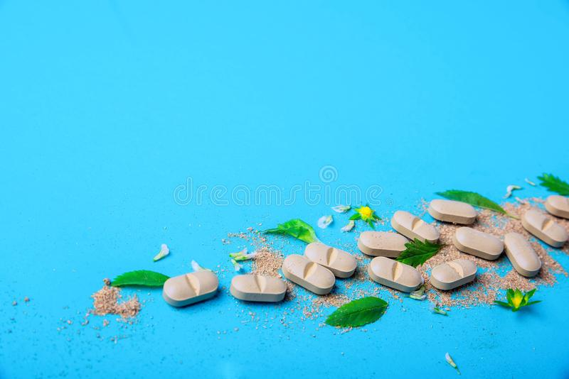 Additivi di erbe naturali dalle erbe, versate da un barattolo bianco Il concetto di cibo sano detox Fotographia a macroistruzione immagini stock