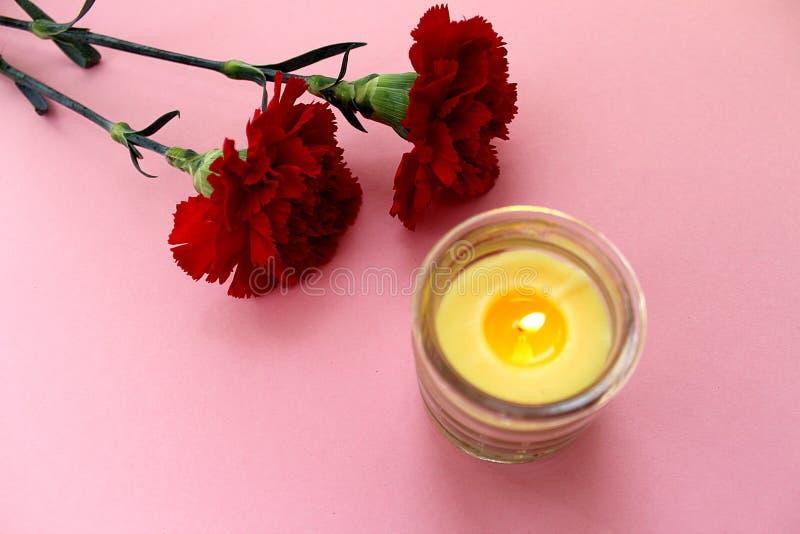 Addolorandosi due garofani rossi con una candela fotografia stock