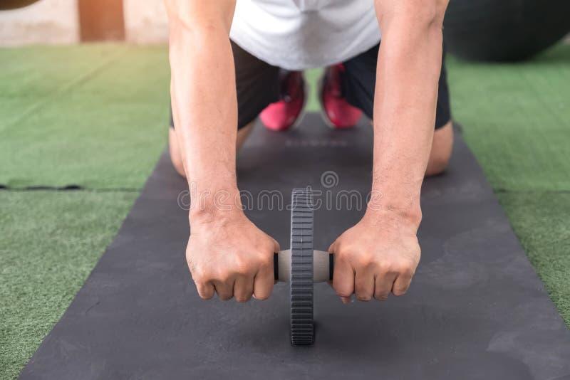 Addome di esercizio degli uomini con un rullo di ab fotografie stock