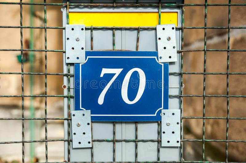 Old vintage house address blue metal number 70 seventy on the gate and mail or letter box of residential building exterior wall on royalty free stock photography