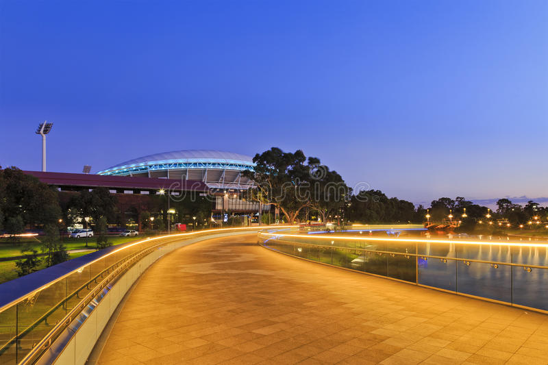 ADE Footbridge North. Width of modern footbridge over Torrens river in Adelaide, South Australia. Bright illumination lights reflecting in calm waters at sunrise royalty free stock photos