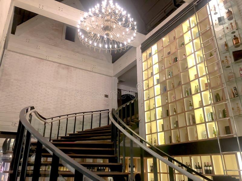 Adega de vinho com a garrafa de vinho na prateleira, o clássico interno com escadas de madeira e o candelabro imagem de stock