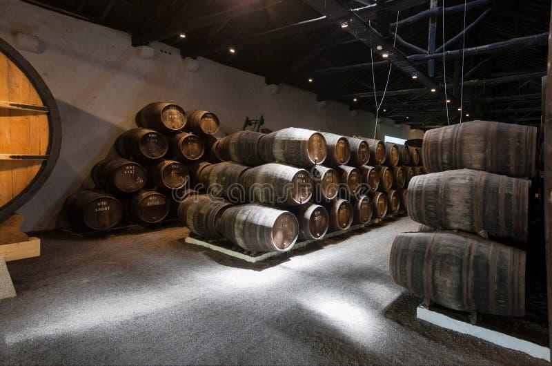 Adega de vinho velha com os tambores de madeira grandes e pequenos para o winemaking tradicional imagens de stock royalty free