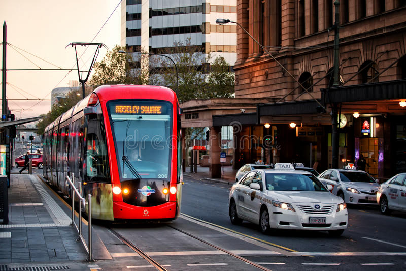 Adelaide tram and taxi. ADELAIDE,AUSTRALIA - JUNE 6,2014: A tram waits outside the railway station in the morning rush hour. Adelaide's tram system was once stock image