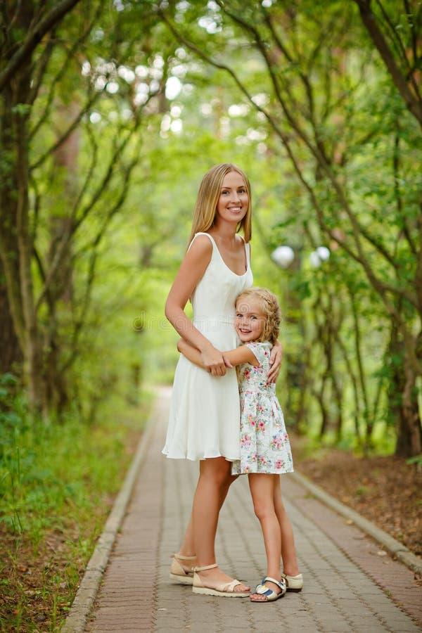 Adelgace la madre y a la hija rubias en el bosque en el verano en el sol imagen de archivo