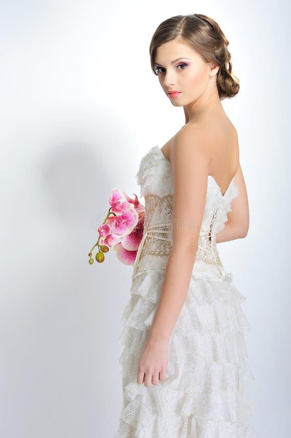 Adelgace a la mujer hermosa con las flores que llevan dres lujosos de la boda imagen de archivo libre de regalías