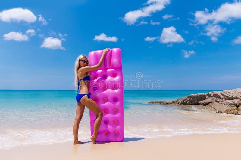 Adelgace a la mujer rubia con la playa del trópico del colchón de aire foto de archivo