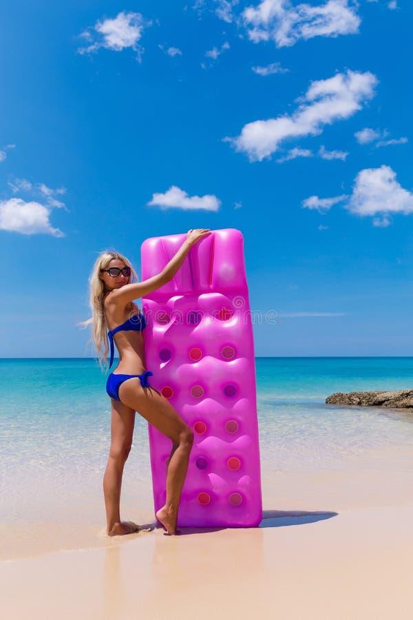 Adelgace a la mujer rubia con la playa del trópico del colchón de aire fotografía de archivo