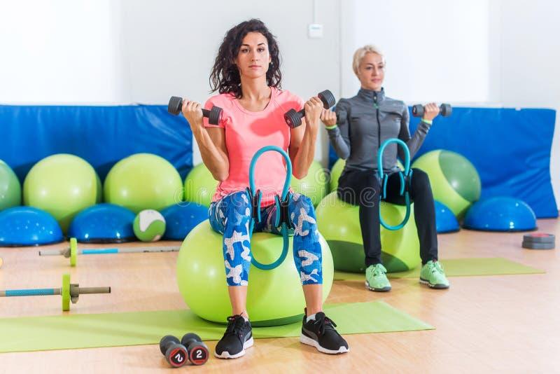 Adelgace a las mujeres deportivas que entrenan a sentarse en las bolas del ejercicio que llevan a cabo pesas de gimnasia y que ex imagen de archivo