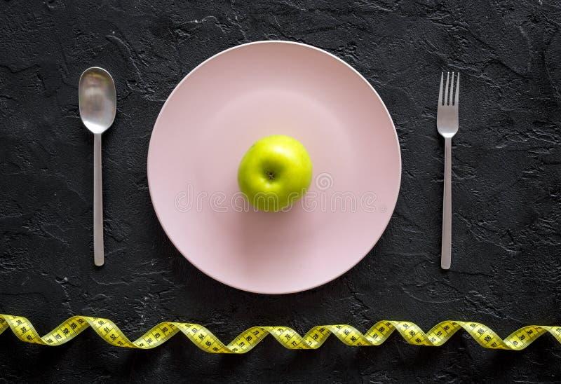 Adelgazar dieta Apple en la placa y la cinta métrica en la opinión superior del fondo negro imágenes de archivo libres de regalías