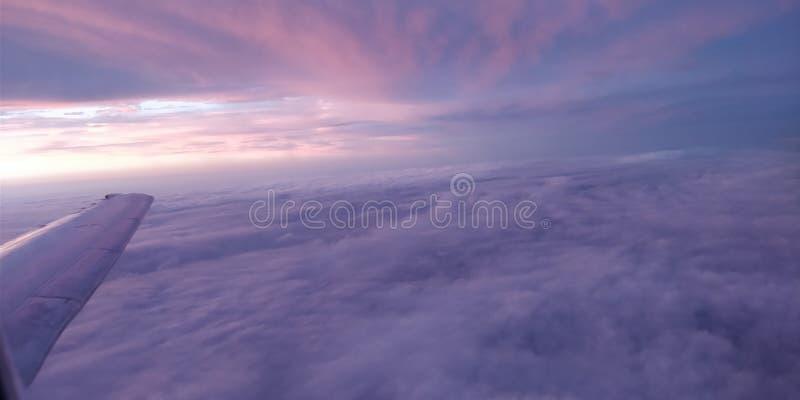 Adembenemend zicht buiten een vliegtuig dat net boven de wolkenlijn vliegt stock afbeeldingen