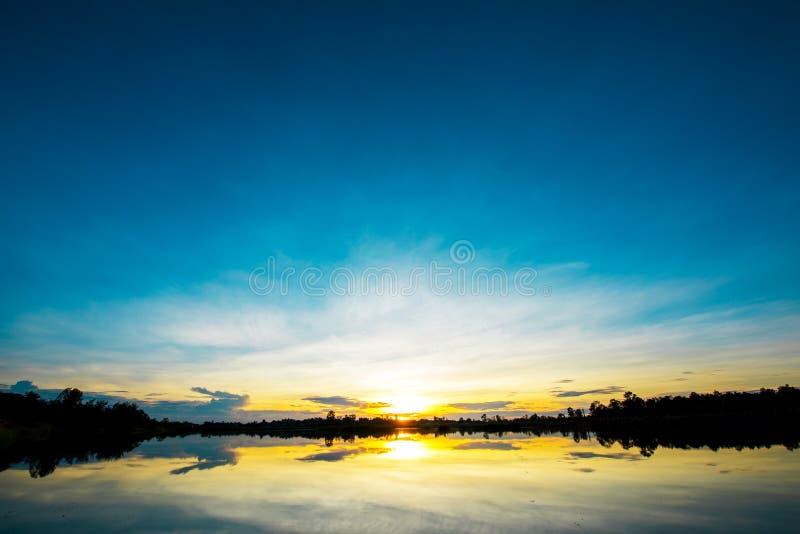 Adembenemend zonsonderganglandschap over kalm meer stock foto's