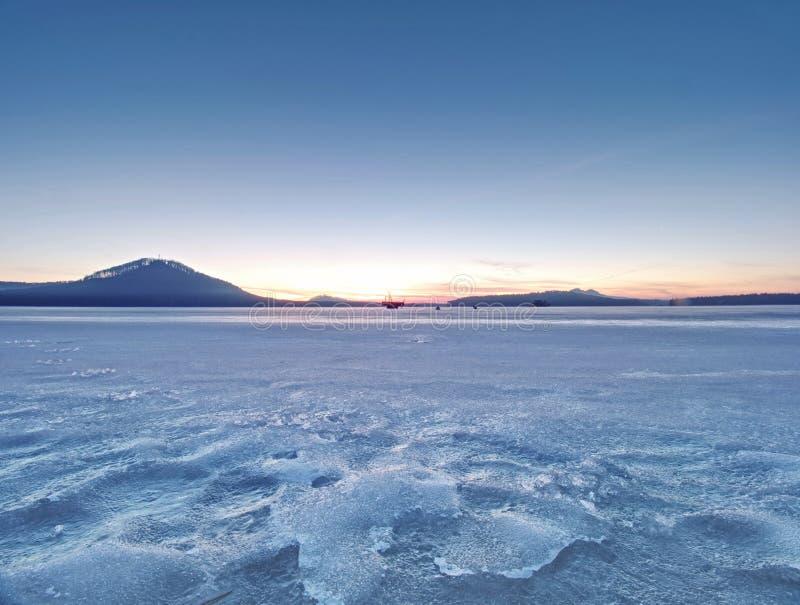 Adembenemende zonsondergang met blauwe roze wolken over bevroren meer royalty-vrije stock afbeeldingen