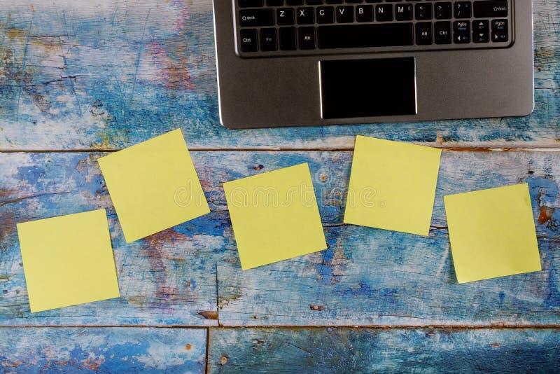 Adesivos quadrados amarelos vazios com teclado de computador no fundo de madeira azul imagem de stock royalty free