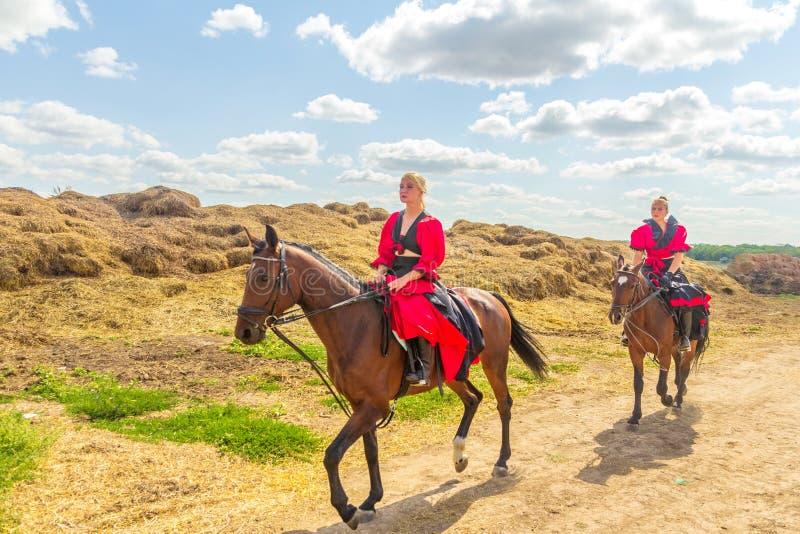 Adestramento do esporte equestre, passagem - duas moças na roupa bonita sentam-se em um cavalo imagens de stock