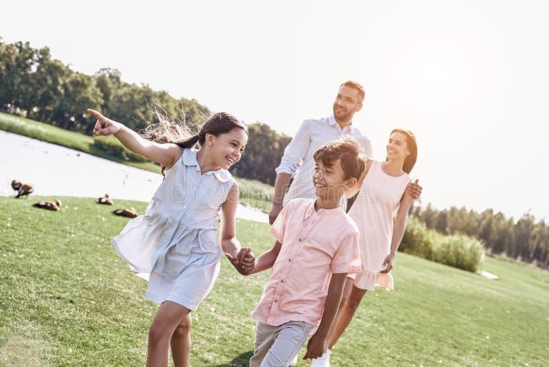 adhérence La famille de quatre marchant sur un champ herbeux près du lac badine photographie stock libre de droits