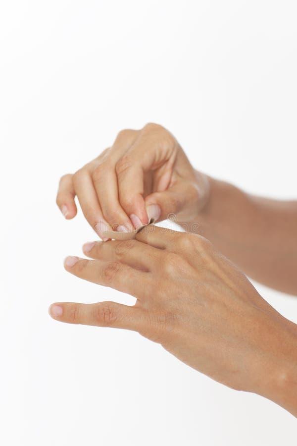 Adhesive bandage on hand. Woman putting adhesive bandage on a hand stock photography