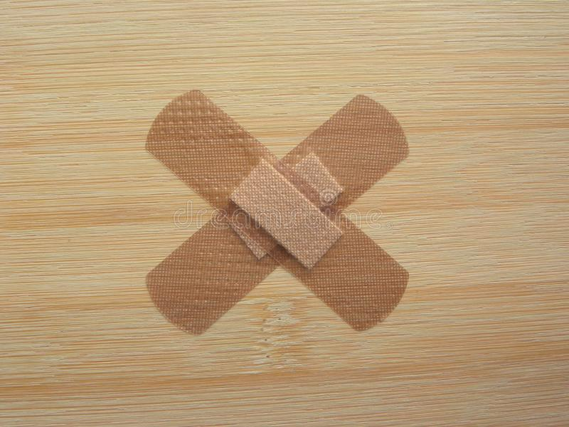 Adhesive bandages. Brown color adhesive bandages in cross shape on wooden table royalty free stock images