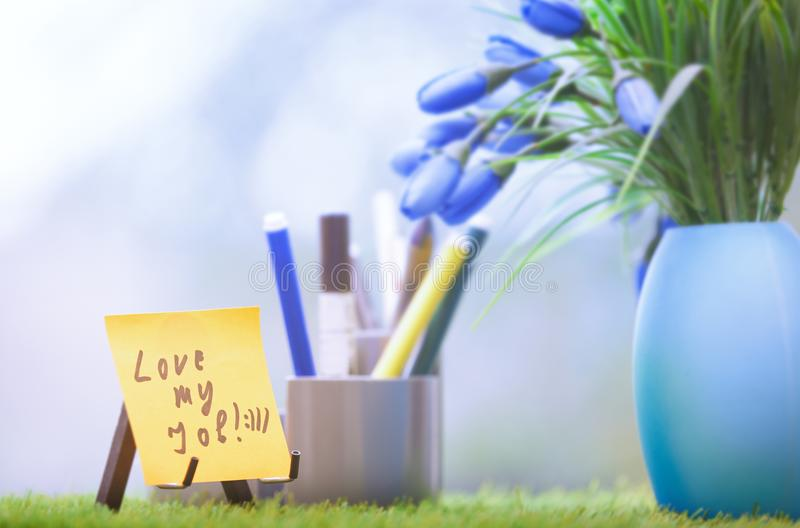 Adhesive note with Love my job text at green office royalty free stock photos