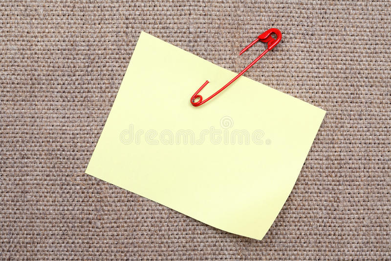 Adhesive Note And Safety Pin. Blank yellow adhesive note attached with red safety pin to canvas background royalty free stock image