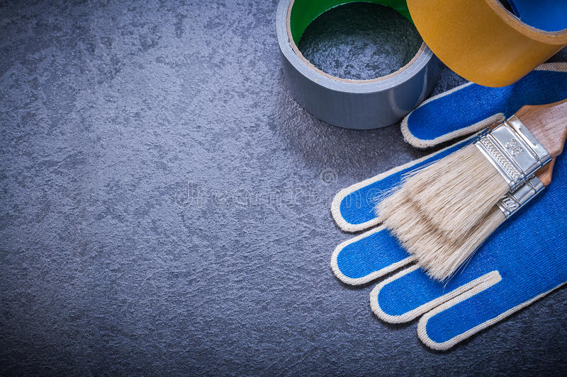 Adhesive tape paintbrushes working gloves on black. Background construction concept royalty free stock images
