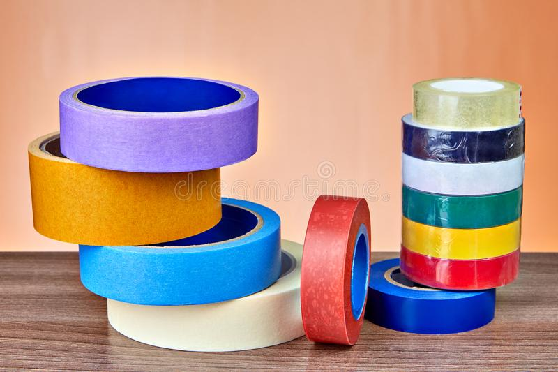 Multicolored rolls of insulation and masking tape lie on table. Adhesive tape in range, set of masking tape and electrical tape in various colors royalty free stock photo