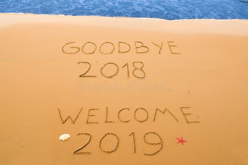 Adiós 2018 y da la bienvenida a 2019 escrito en la arena fotografía de archivo libre de regalías