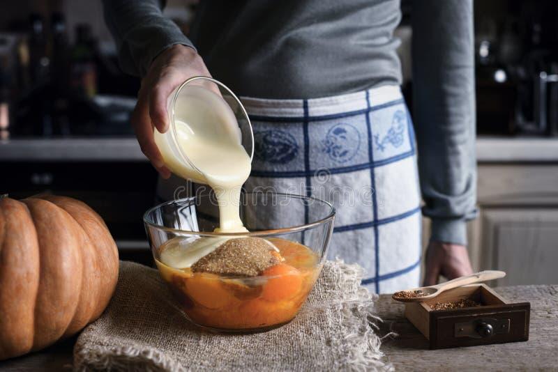 Adición de la leche condensada en la pasta para la torta de la descarga de la calabaza imagenes de archivo