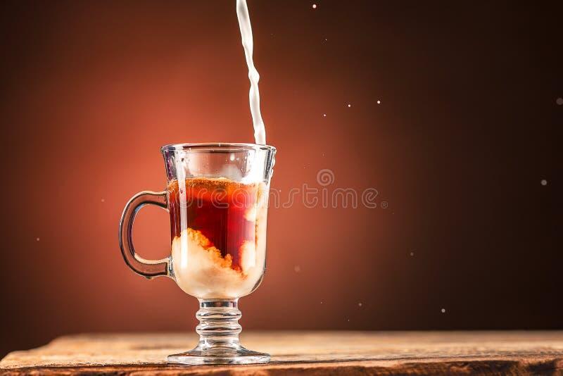 Adición de la leche a una taza de té fotos de archivo libres de regalías