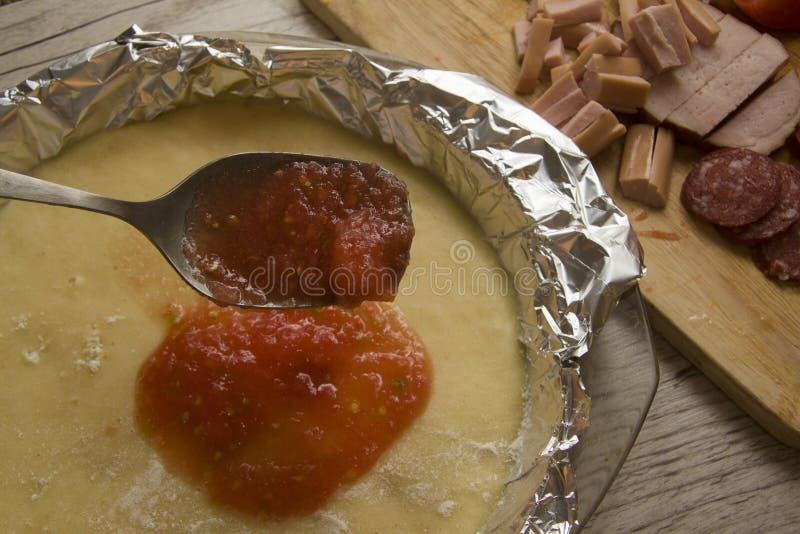 Adición de la salsa de tomate a la pizza imagenes de archivo