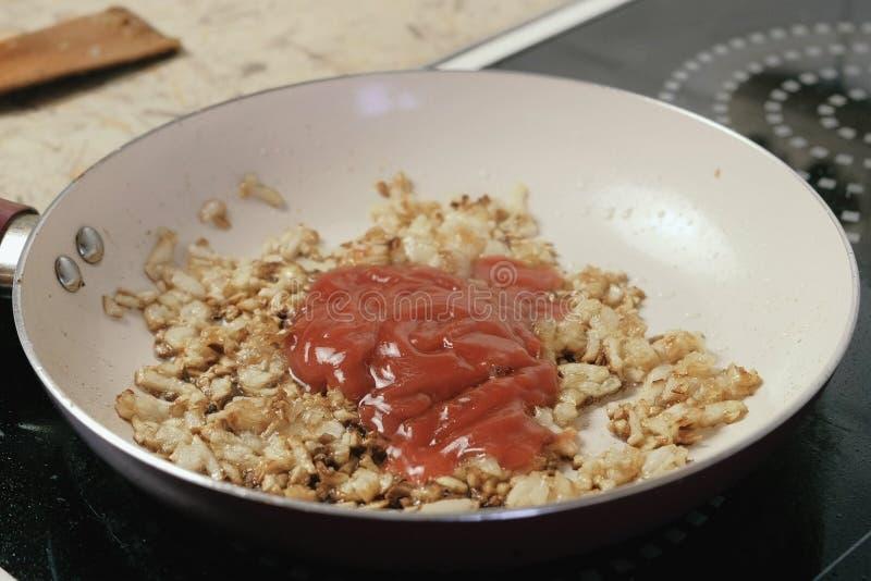 Adición de la salsa de tomate a la cebolla frita de oro en la cacerola fotos de archivo