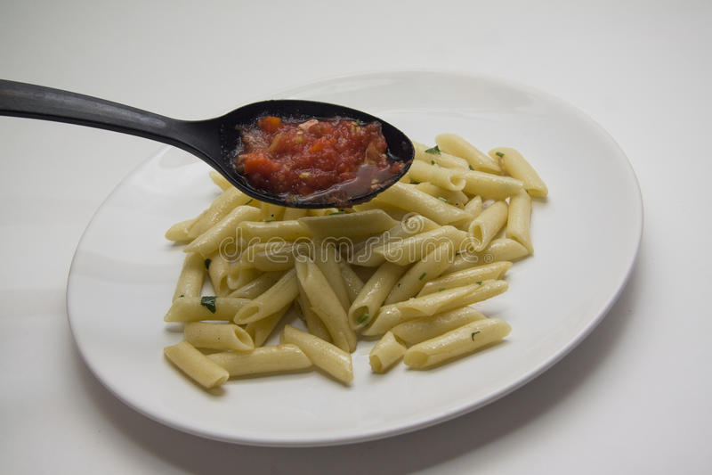 Adición de las pastas del tomate a los tallarines fotografía de archivo