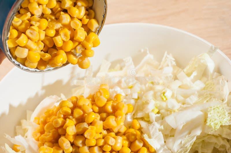 Adición de maíz conservado a la ensalada de col blanca fotografía de archivo