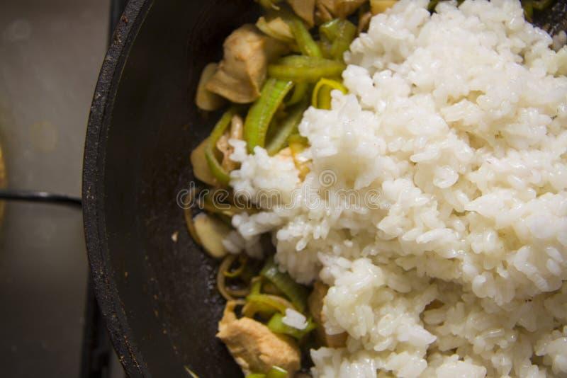 Adición del arroz a la cacerola con el pollo fotos de archivo libres de regalías