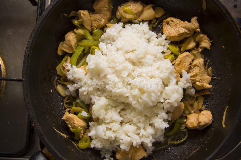 Adición del arroz a la cacerola con el pollo fotografía de archivo