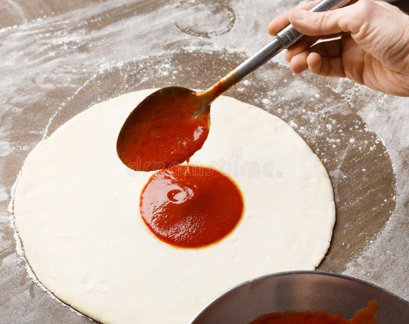 Adición del sause en base de la pizza Salsa de tomate de extensión del cocinero foto de archivo libre de regalías