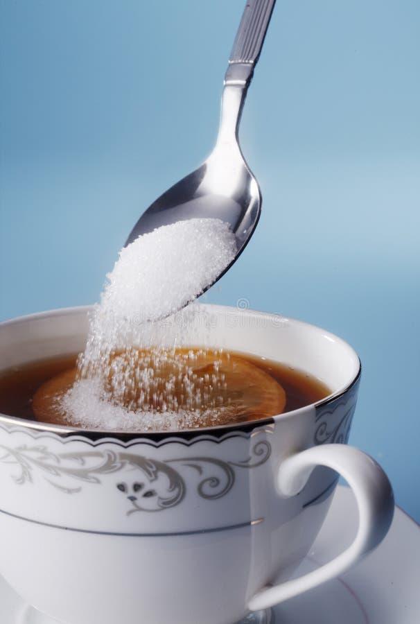 Adicionando o açúcar imagem de stock