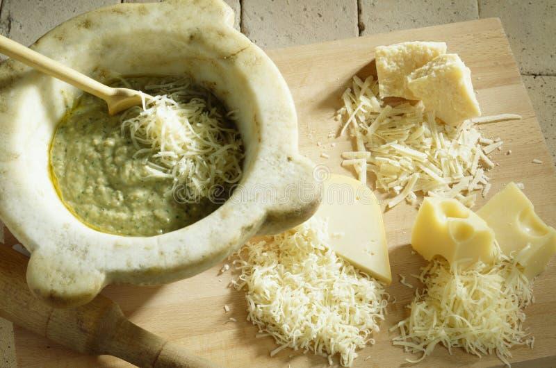 Adicionando o queijo raspado à preparação imagens de stock