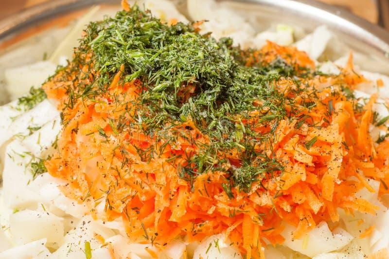 Adicione o óleo de girassol à salada vegetal Couve, cenouras e cebolas imagens de stock