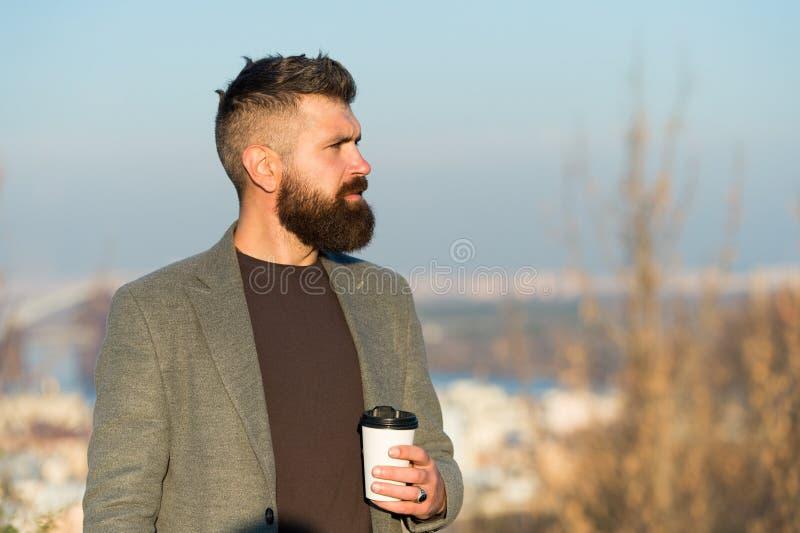 adicta a la cafeína Suspensión de hipster con bebida energética de cafeína Hombre con barba recarga con bebida caliente de cafeín imagenes de archivo