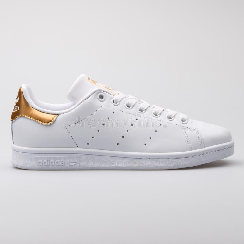 Adidas Stan Smith white and gold sneaker stock image