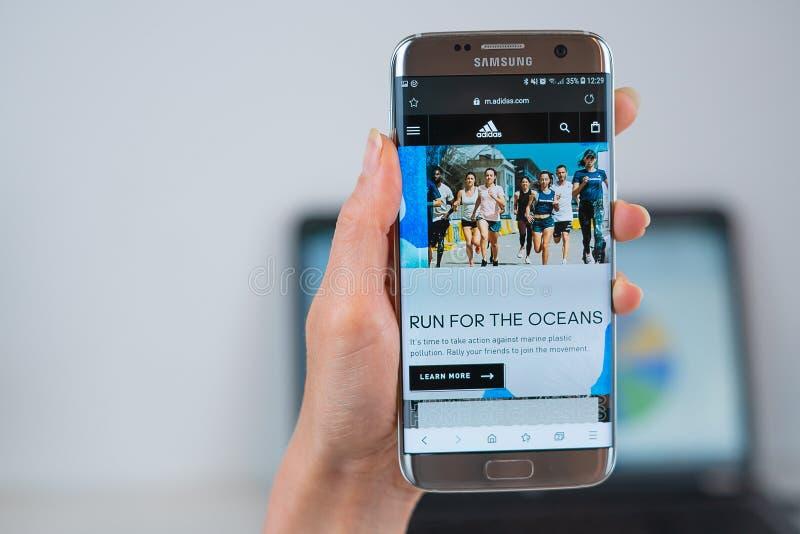 Adidas webbplats som ?ppnas p? mobilen arkivbilder