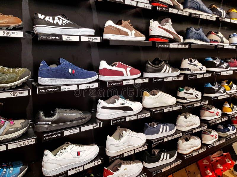 Adidas, zapatos deportivos Puma en fila en el centro comercial local imagenes de archivo